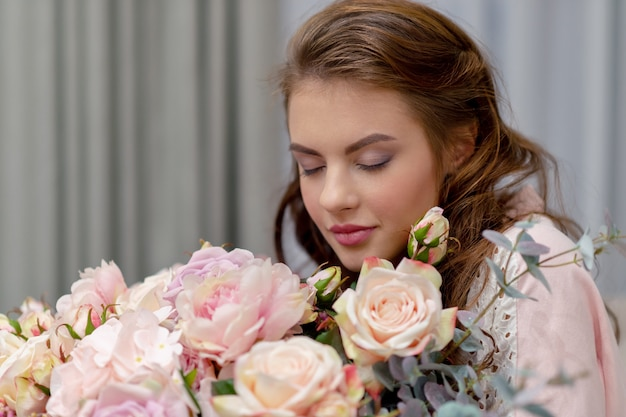 Attraente giovane donna con bouquet di centinaia di fiori sta trascorrendo del tempo a casa.