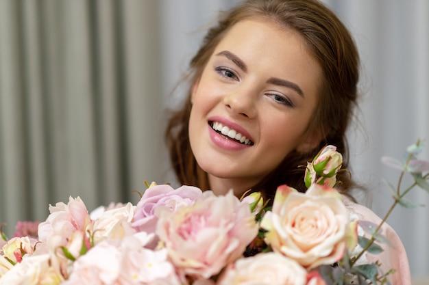 何百もの花の花束を持つ魅力的な若い女性は家で時間を過ごしています。