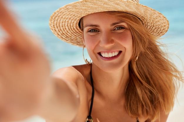 Attraente giovane donna con un ampio sorriso, pelle sana, riposa in riva al mare, scatta foto di se stessa, è di buon umore, gode del tempo libero e delle vacanze estive. bella femmina fa selfie contro l'oceano