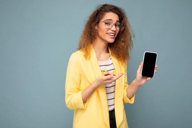 Attractive young woman with curly dark blond hair wearing yellow jacket and optical glasses isolated on background holding and showing mobile phone with empty space for cutout looking at camera.