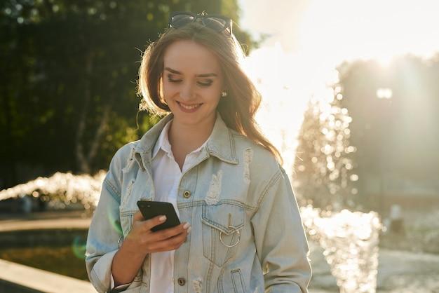 분수에 의해 그녀의 터치 스크린 모바일 휴대 전화를 사용 하여 곱슬 머리를 가진 매력적인 젊은 여자.