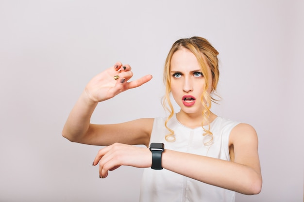 Attractive young woman with curly hair wearing stylish blouse looks at black wristwatch and plans day. charming blonde lady in white tank top remembers list of cases for today and calculates time.