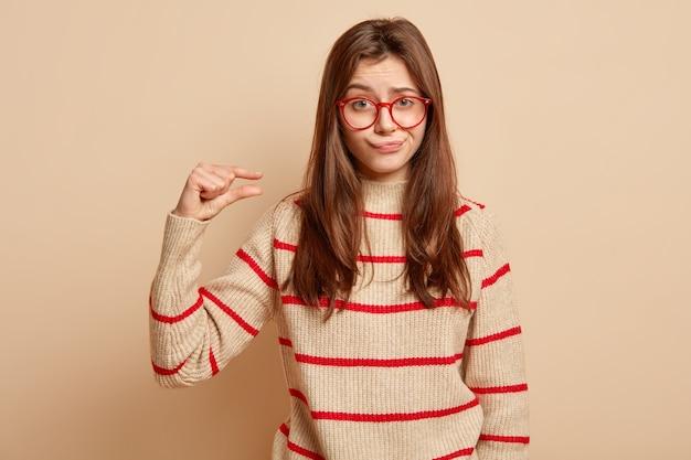 Attraente giovane donna con espressione insoddisfatta, mostra un piccolo piccolo gesto, porta le labbra per il dispiacere, indossa occhiali con orlo rosso e maglione a strisce, isolato sopra il muro beige