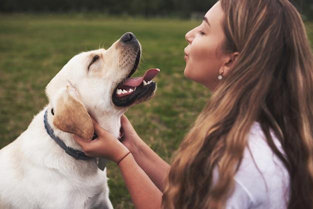 屋外の犬を持つ魅力的な若い女性。ラブラドル・レトリーバー犬と緑の芝生の上の女性