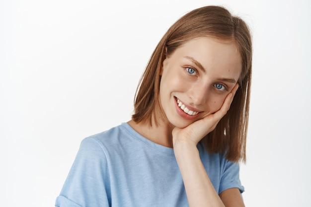 Attraente giovane donna con capelli biondi corti e pelle naturale liscia e luminosa, tocca il viso e sorride denti bianchi, in piedi contro il muro bianco