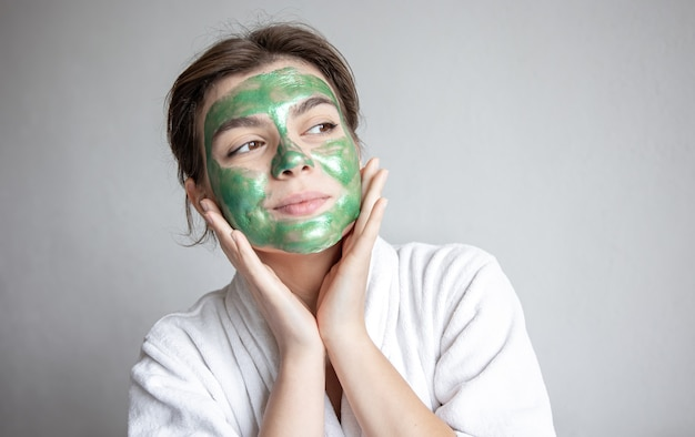 Attractive young woman with a green cosmetic mask on her face