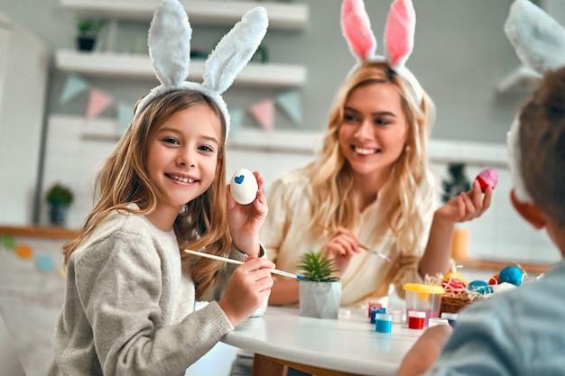 작은 귀여운 소녀와 소년 매력적인 젊은여자가 부활절 축 하를 위해 준비 하 고 있습니다. 토끼 귀를 입고 행복한 가족은 계란을 그리는 동안 부활절 전에 함께 시간을 보내고 있습니다.