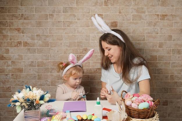 かわいい女の子と魅力的な若い女性はイースターのお祝いの準備をしています。うさぎの耳をかぶったママと娘が家で楽しんでいます。