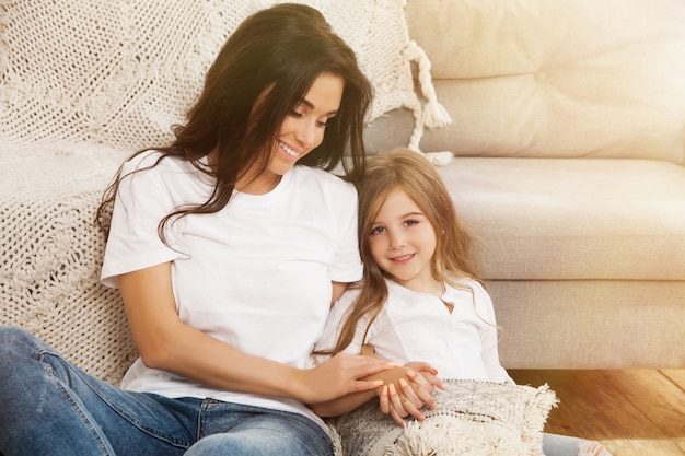 Attractive young woman with little cute girl are spending time together at home