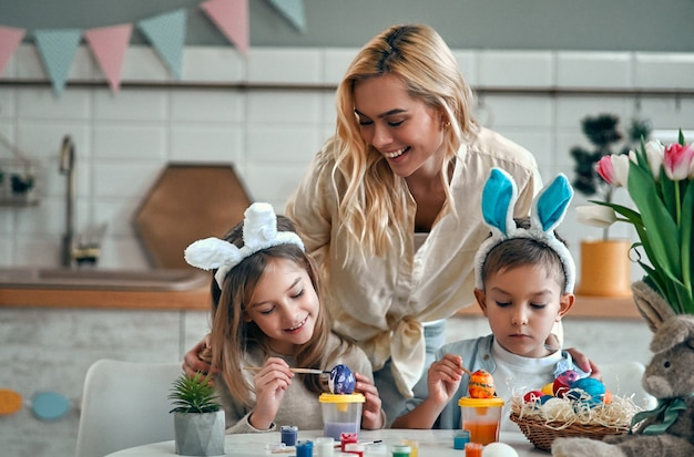Attractive young woman with little cute girl and boy are preparing for easter celebration. happy family wearing bunny ears are spending time together before easter while painting eggs.