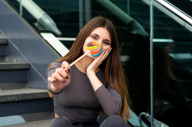 Attractive young woman with lollipop sitting on steps outdoors