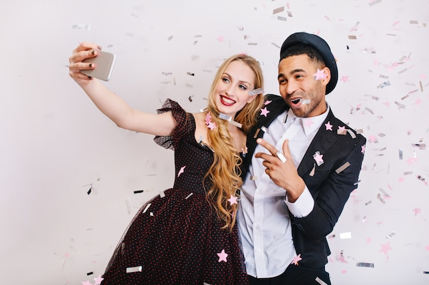 Attractive young woman with long blonde hair in luxury evening dress making selfie in tinsels with joyful handsome man. celebrating party