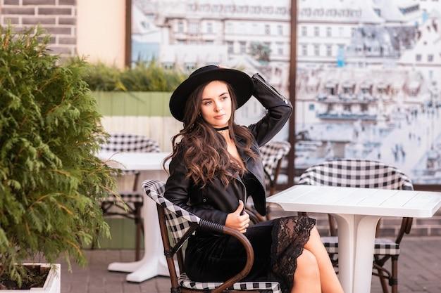 カフェに座っている黒い革のジャケットと帽子の長い巻き毛を持つ魅力的な若い女性。
