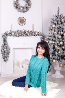 Attractive young woman with long hair sitting on a floor indoors in a christmas interior