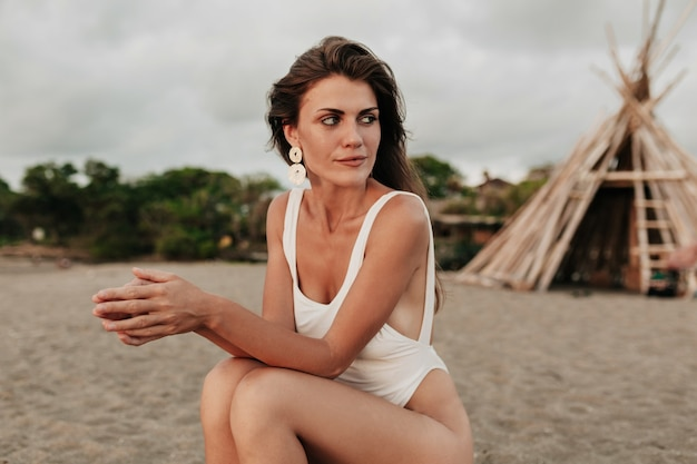 Attraente giovane donna con i capelli lunghi che indossa costume da bagno bianco e bei guadagni che si siede sulla spiaggia sabbiosa