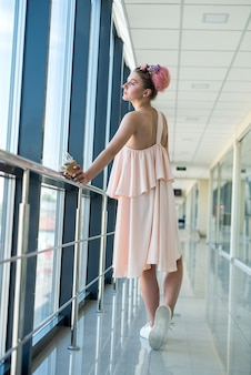 Attractive, young woman with luxurious makeup and hairstyle inside building