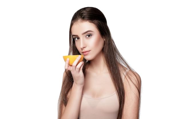 オレンジ色の背景に分離された魅力的な若い女性。健康食品