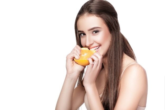 Attractive young woman with orange isolated on white background. healthy food