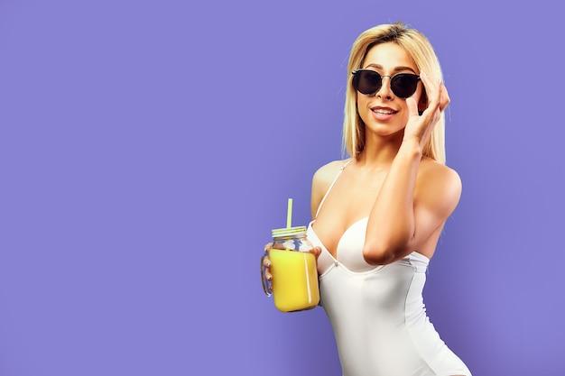 Привлекательная молодая женщина с апельсиновым соком в питьевой банке на фиолетовой стене.