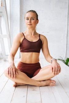 家で休んでいるスポーツウェアを身に着けている完璧な運動体を持つ魅力的な若い女性は、窓枠で蓮のポーズで足を組んで座って、カメラを見ています。家庭での健康的なライフスタイルの概念。