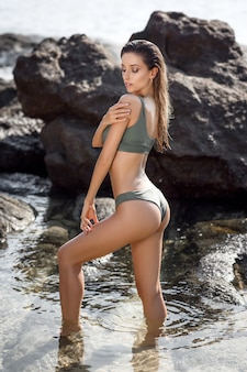Attractive young woman with perfect tan fit body posing on the beach