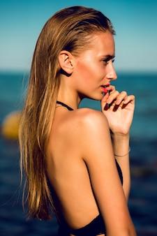 Привлекательная молодая женщина с идеальным загаром подходящим телом позирует на пляже с голубым небом.