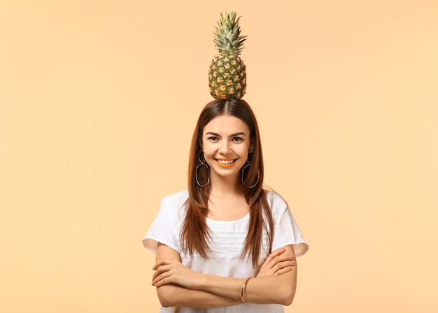 Привлекательная молодая женщина с ананасом на цветной поверхности