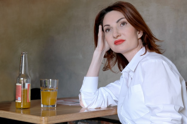 Attractive young woman with red hair in white shirt sits at wooden table in bar with glass of lemonade. the woman rested her head on her hand and looked thoughtfully to side. girl waiting for date