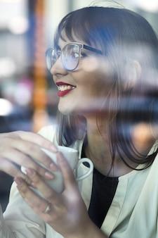붉은 입술을 가진 매력적인 젊은 여성이 안경을 쓰고 레스토랑에서 창문을 통해 커피를 마신다