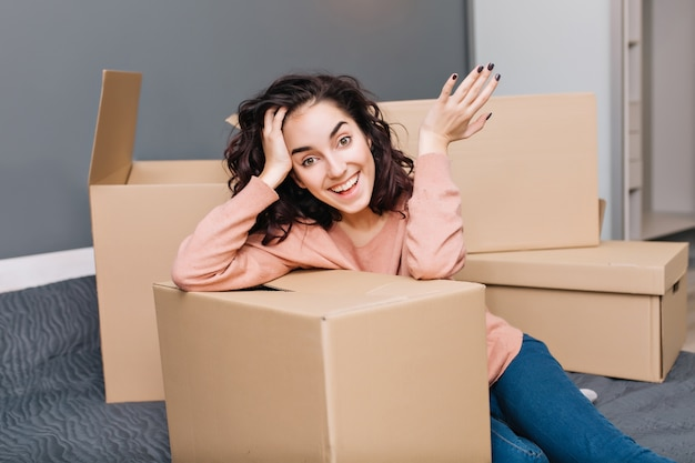 モダンなアパートで包まれたカートンを表現する短いブルネットの巻き毛を持つ魅力的な若い女性。移転を楽しんで、新しい家に引っ越して、本当の幸せな感情