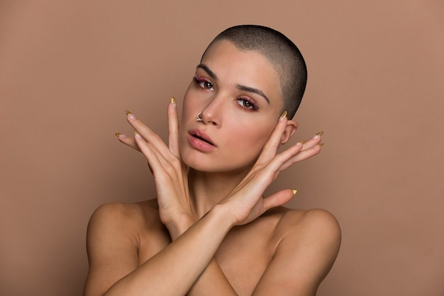 Attractive young woman with short hair posing on beige