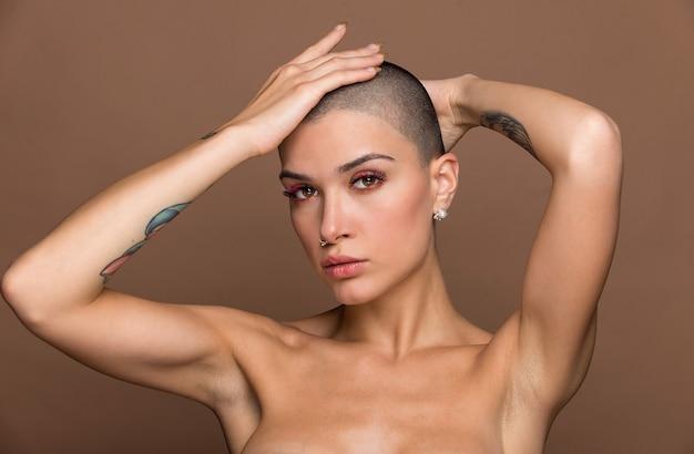 ベージュでポーズをとって短い髪の魅力的な若い女性
