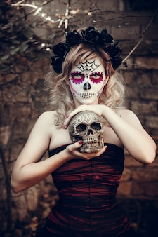 Привлекательная молодая женщина с сахарной череп макияж. мексиканский день мертвых женщин, носящих сахарный череп макияжа и цветочный венок.