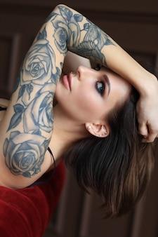 Привлекательная молодая женщина с татуировкой позирует