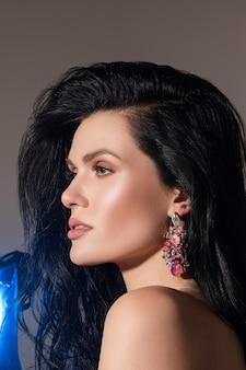 Привлекательная молодая женщина с густыми темными волосами и голым плечом демонстрирует красивые серьги с розовыми кристаллами.