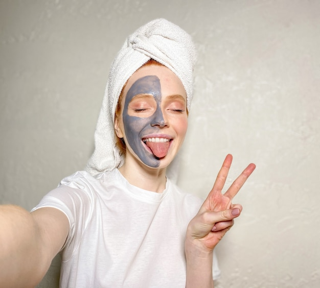 Attractive young woman with a towel on her head and a clay mask