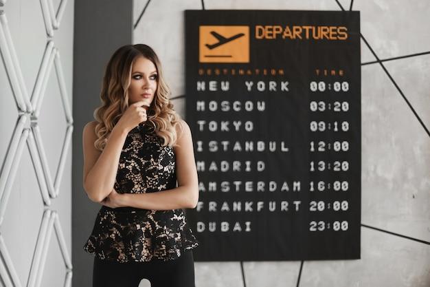 Привлекательная молодая женщина с модным макияжем в модном наряде позирует на фоне доски вылета
