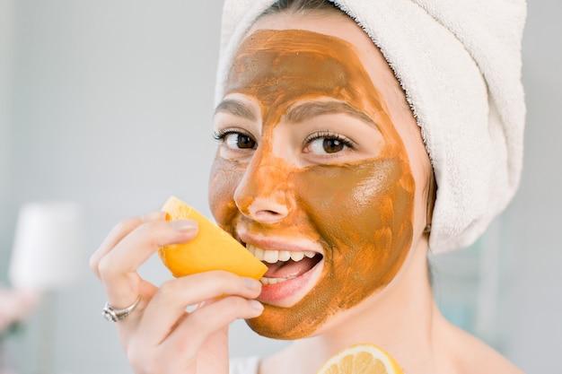 頭に白いタオルと泥の顔の茶色のマスクを持つ魅力的な若い女性はレモンと笑顔をかみます。美容、スパ、スキンケア、ボディケア。