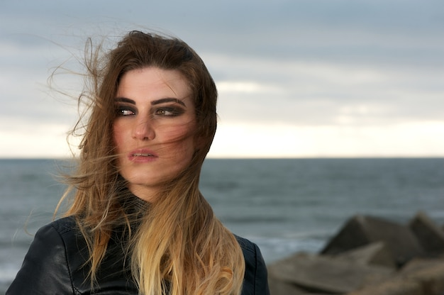 Attractive young woman with wind blowing hair outdoors