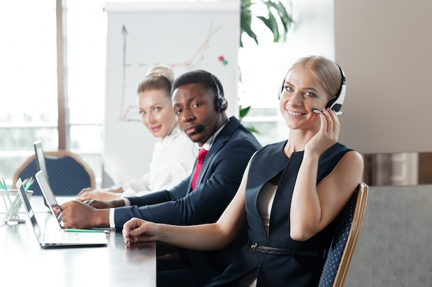 Attractive young woman working in a call center with his colleagues