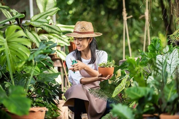 정원 센터에서 장식 식물을 사용하는 매력적인 젊은 여자. 여름 자연에서 외부 원예에 식물을 검사하는 여성 감독자. 웃 고 아름 다운 정원사입니다. 식물 관리.