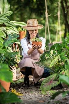 Привлекательная молодая женщина, работающая с декоративными растениями в садовом центре. женщина-супервайзер изучает растения в саду на улице в летнюю природу. красивый садовник улыбается. уход за растениями.