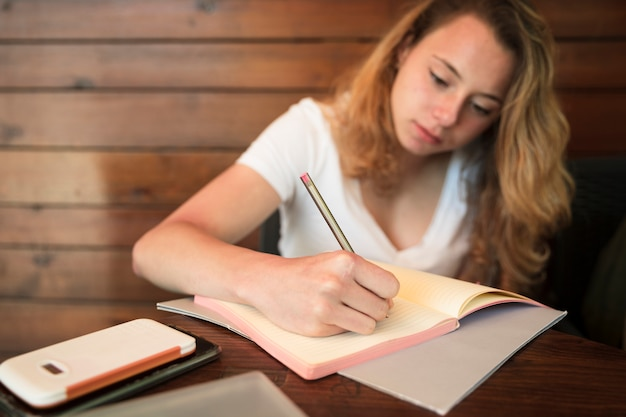 Attractive young woman writing in notebook