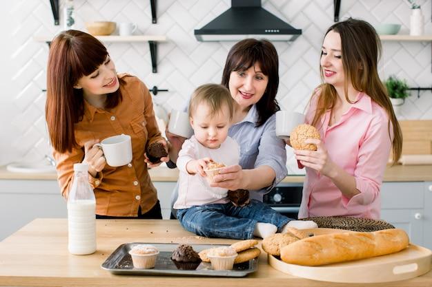 魅力的な若い女性、中年女性、かわいい娘がキッチンで調理しています。台所でマフィンを食べてコーヒーを飲む愛情のある家族