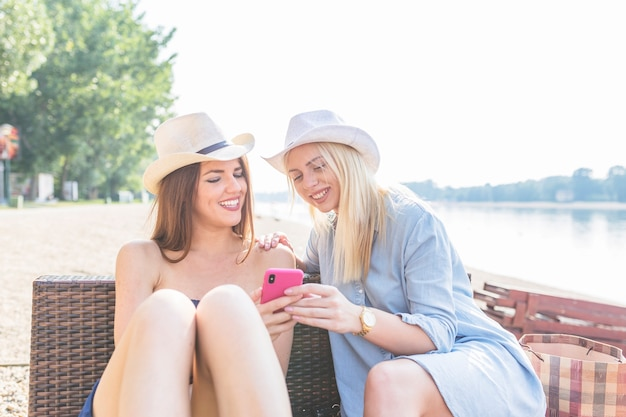 An attractive young women sitting on beach looking at mobile phone