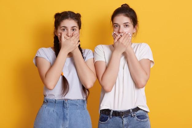 Привлекательные молодые молодые девушки в белых футболках и джинсах