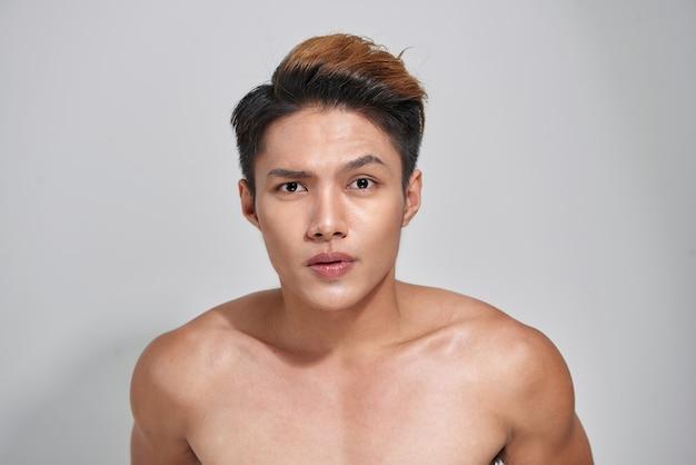 魅力的な若々しい裸の男性が自信を表現しています