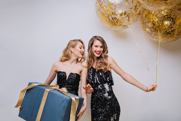 Attractive ypung women in black luxury dresses celebrating birthday party with big present and balloons. excited, having fun, charming models, celebrating, smiling.
