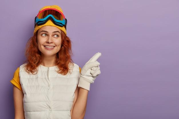 Рыжая женщина attractve в теплой шапке, лыжных очках и белом джемпере