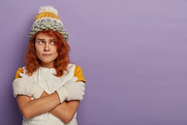 Attrarre la donna dai capelli rossi indossa cappello caldo, occhiali da sci e maglione bianco